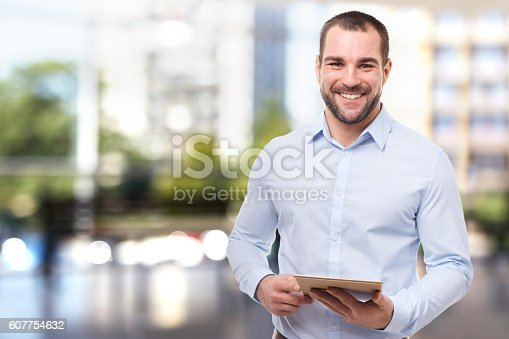 istock Man in office with tablet computer 607754632