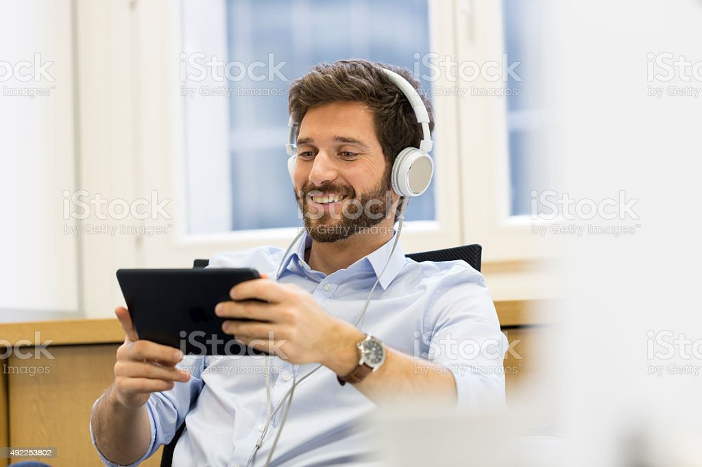Man in office with tablet pc and headphones stock photo