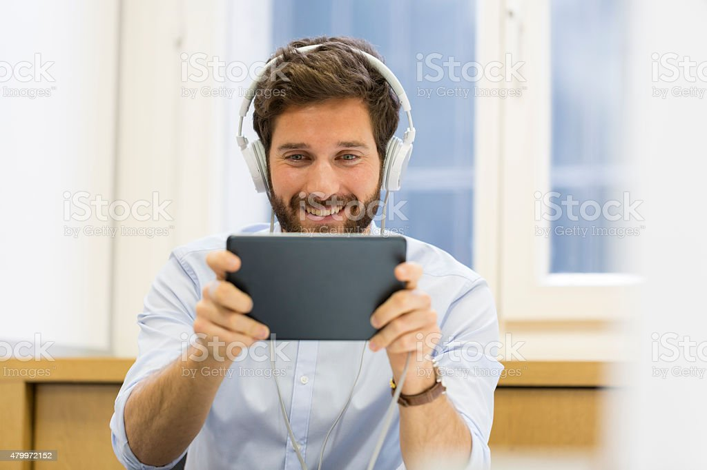 Man in office withe tablet pc and headphones stock photo