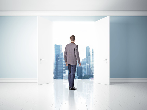 man in opened doors in blue wall, way to success