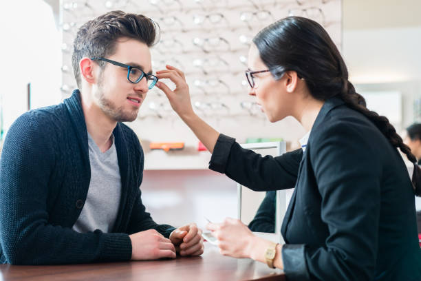 Man in optician shop getting advice from saleswoman stock photo