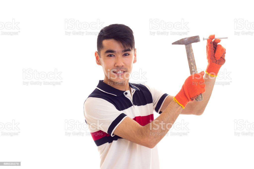 Man in orange gloves holding hammer and nail zbiór zdjęć royalty-free