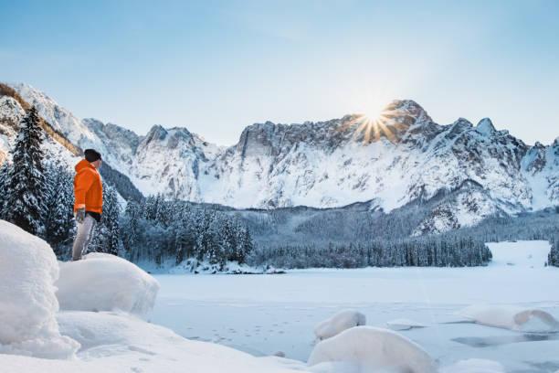 Mann in orange Jacke auf zugefrorenen See Blick zum Berg – Foto