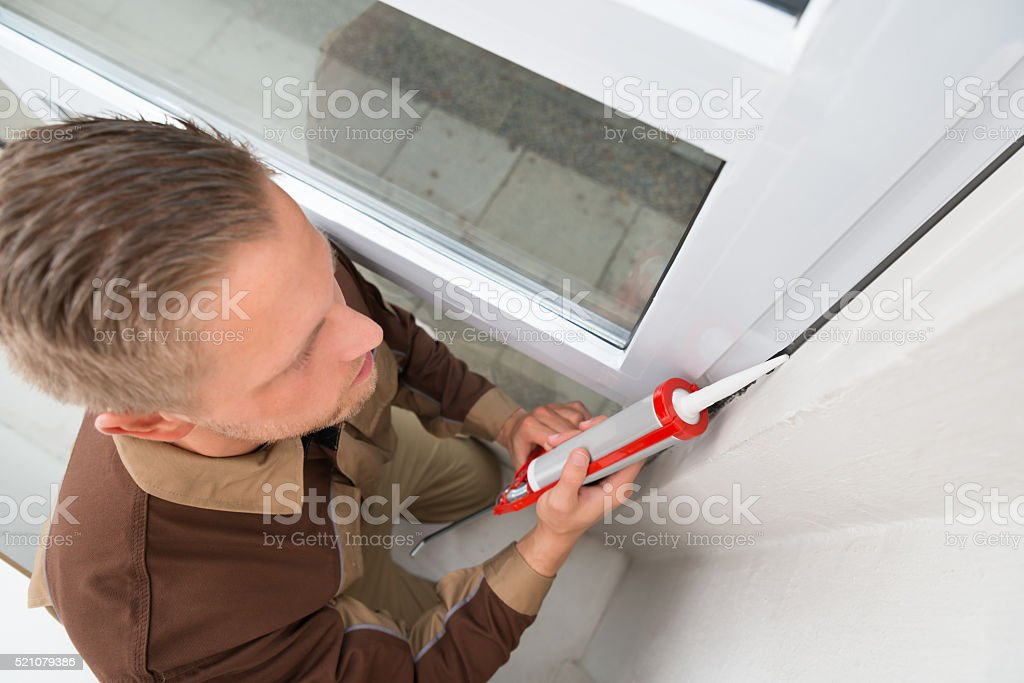 Man In Overall Applying Silicone Sealant stock photo