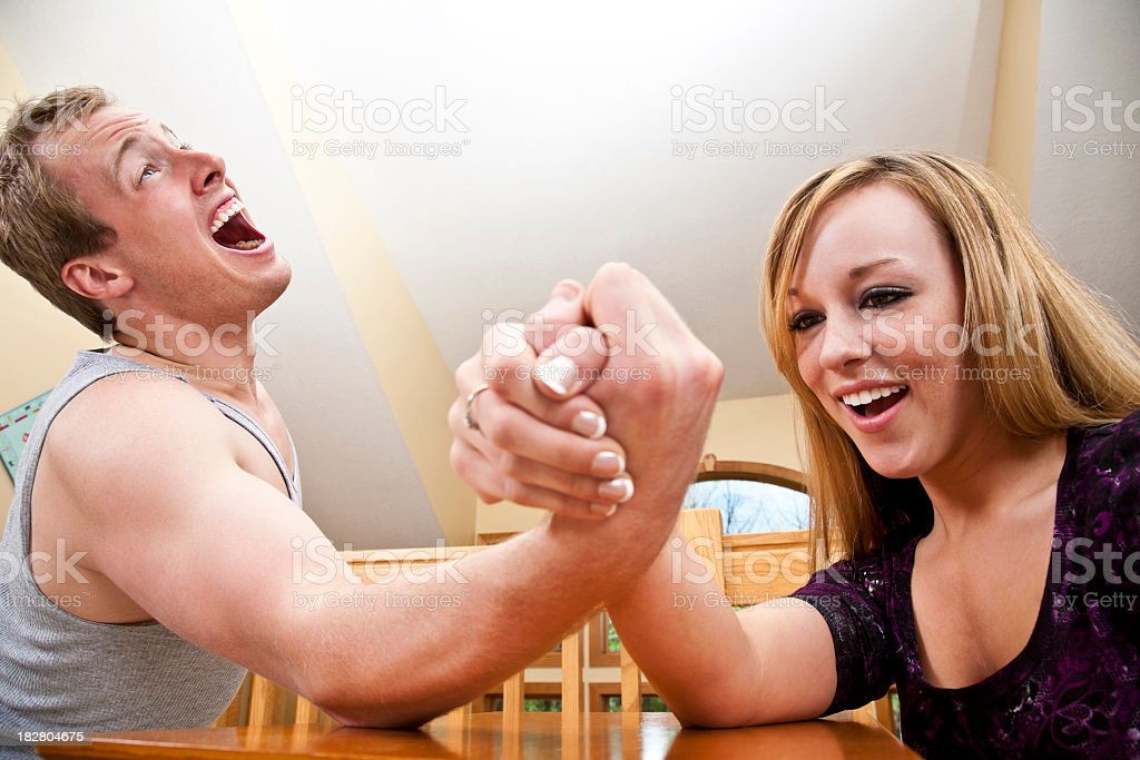 Man in Pain While Losing Arm Wrestling Competition to Girl stock photo