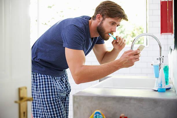 man in pajamas brushing teeth and using mobile phone - cell phone toilet stockfoto's en -beelden