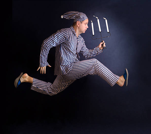 man in pajamas running with a candlestick - pajamas stock photos and pictures
