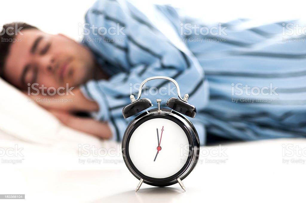 Homem em pijama acomoda do barulho de despertador - foto de acervo