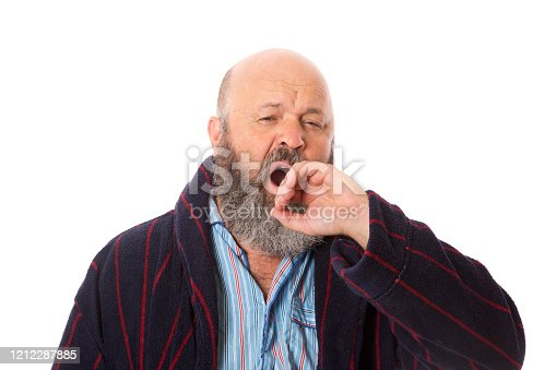 A mature guy in dressing gown yawning.