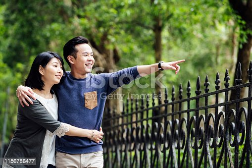 Happy Chinese couple in their 20s and 30s enjoying weekend in park, discovery, togetherness, love