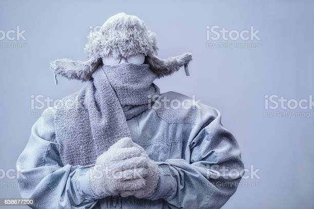 Photo of Man in parka, hat and scarf frozen from the cold