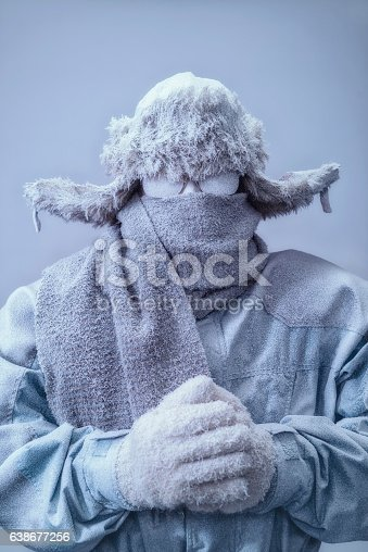 A frozen man with his hands clasped all bundled up in a fur trappers hat, scarf, parka and knit gloves, covered in snow and frost trying to stay warm on a very cold gray Winter's day.