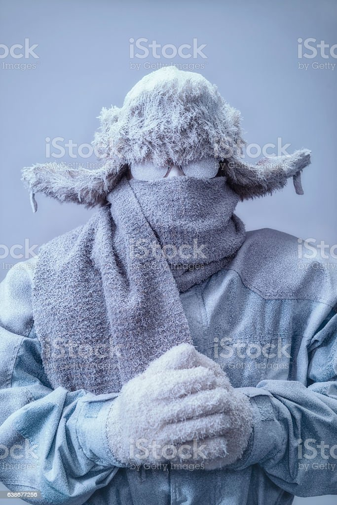 Man in parka, hat and scarf frozen from the cold stock photo
