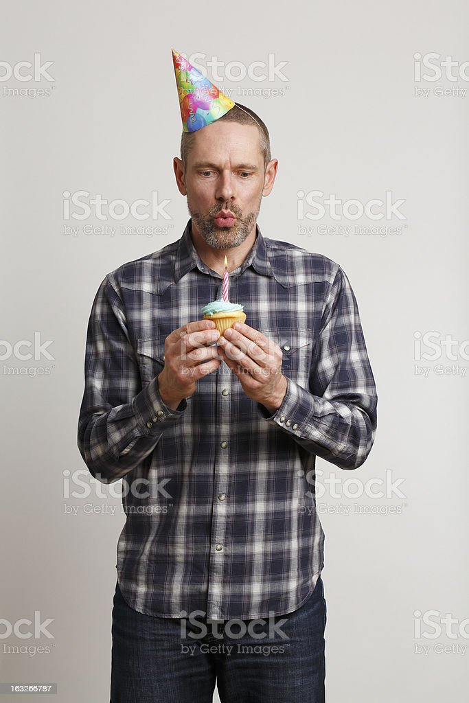 Man in Party Hat Blowing Out Candle on Cupcake royalty-free stock photo