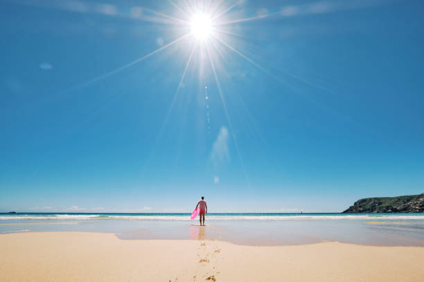 man in pink shorts, t-shirt with rubber ring on an empty perfect beach with bright sunstar against a blue sky, pedn vounder, cornwall. - rubber ring stock photos and pictures