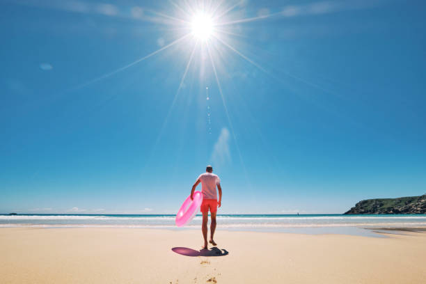 man in pink shorts, t-shirt with rubber ring on an empty perfect beach with bright sunstar against a blue sky, pedn vounder, cornwall. - rubber ring stock pictures, royalty-free photos & images