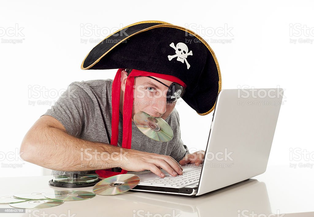 man in pirate hat downloading music on a laptop stock photo