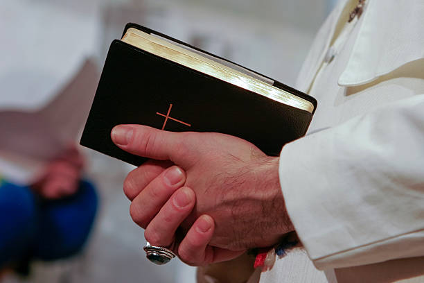 Man in popes garment holding holy bible stock photo