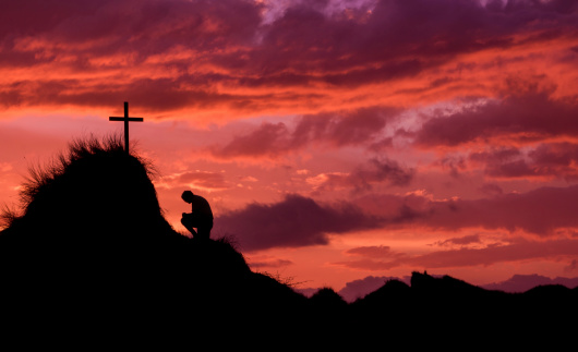 Man below a cross on a hill, praying as the sunsets.