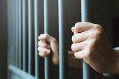 刑務所で男の後ろに手ホールド スチール ケージ刑務所バー。犯罪者の犯罪者は、刑務所でロックされています。