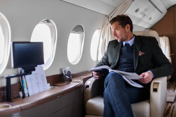 Man in private jet airplane Man sitting inside private jet airplane and looking outside the window while reading a magazine. first class stock pictures, royalty-free photos & images