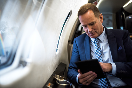 Elegant senior man sitting inside private jet airplane and holding digital tablet.