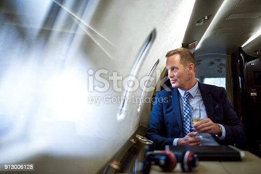 istock Man in private jet airplane 913006128
