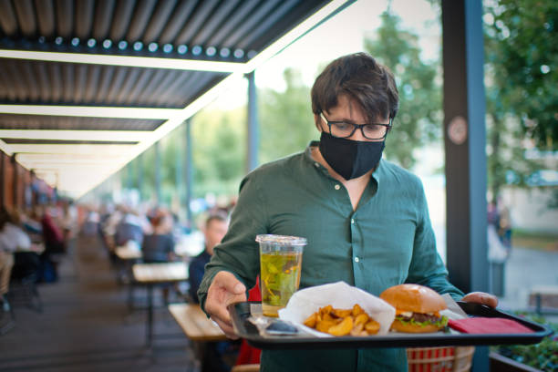 Man in protective face mask with food on trey of an open terrace of a cafe or restaurant