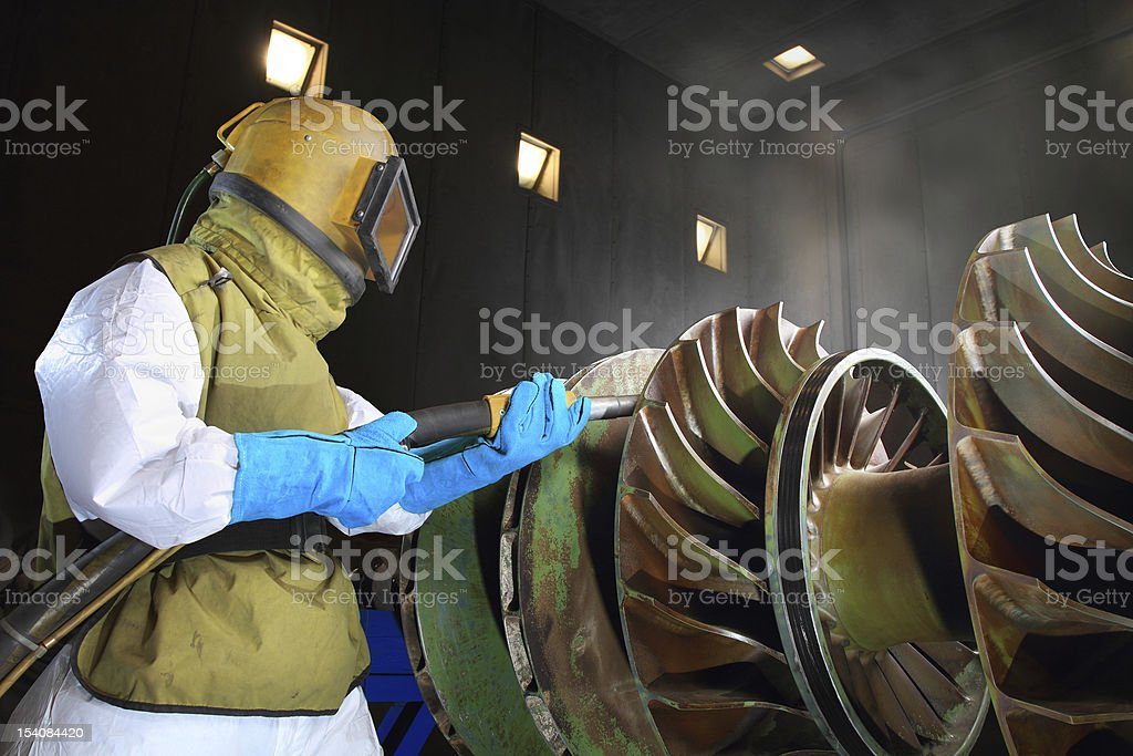 Man in protective gear sandblasting a giant metal wheel stock photo