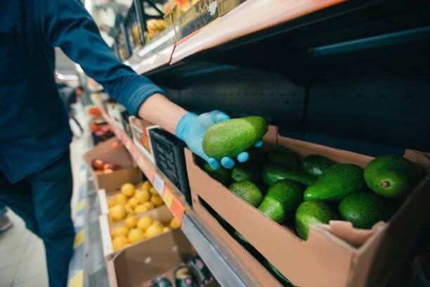 Mann in Schutzhandschuhen nimmt eine Avocado vom Tresen – Foto