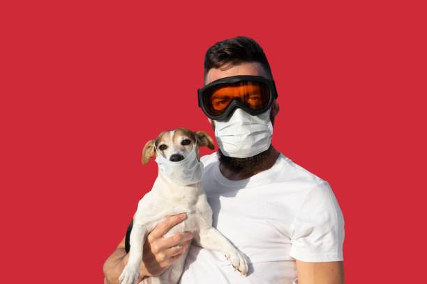 man in protective mask and glasses holds cute jack russell dog in medical mask - covid hair imagens e fotografias de stock