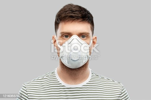 health protection, safety and pandemic concept - young man in protective mask or respirator with valve over grey background