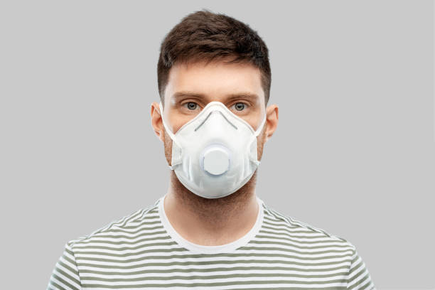 mann in medizinischer schutzmaske oder atemschutz - luftventil stock-fotos und bilder