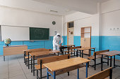 istock Man in protective suit and mask sanitising and sterilises classroom and items inside to prepare for education 1283091640