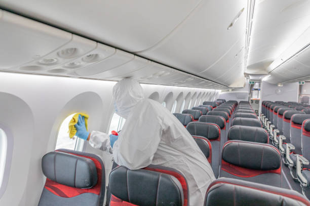 Man in protective suit and mask sanitising plane interior stock photo