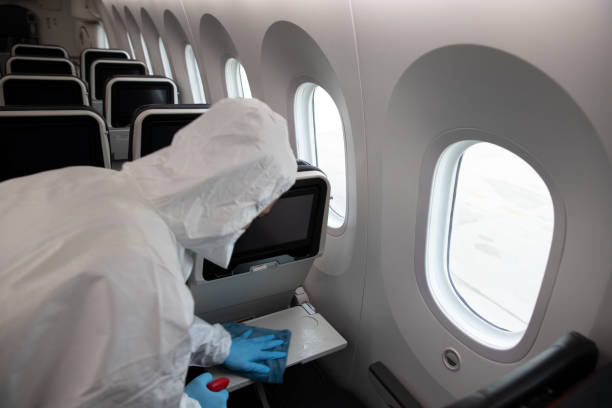 Man in protective suit and mask sanitising plane windows stock photo