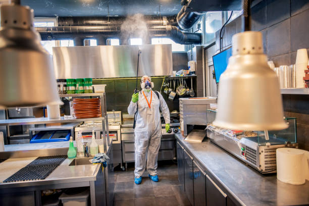 Man in protective suit disinfecting and spraying restaurant kitchen stock photo