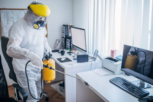 Man in protective suit disinfecting office work space One man, man in protective suit disinfecting office work space alone. crop sprayer stock pictures, royalty-free photos & images