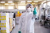 Man in protective suit, mask and gloves standing in food production factory and showing thumbs up. He just disinfected whole facility from covid-19 / corona virus.