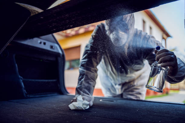 Man in protective suit with mask disinfecting inside car, wipe clean surfaces that are frequently touched, prevent infection of Covid-19 virus coronavirus,contamination of germs or bacteria. Infection prevention and control of stock photo