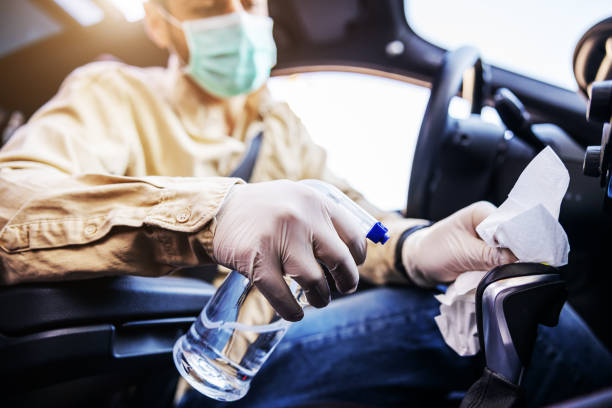 Man in protective suit with mask disinfecting inside car, wipe clean surfaces that are frequently touched, prevent infection of Covid-19 virus coronavirus,contamination of germs or bacteria. Infection prevention and control of viruses. stock photo