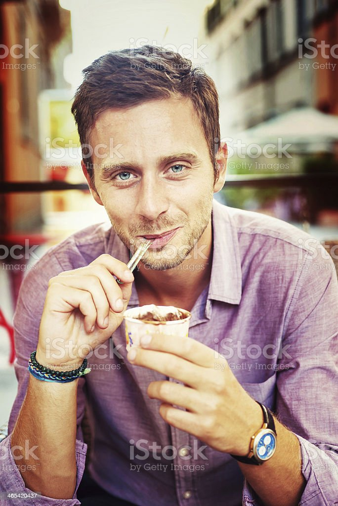 Man in purple shirt smiling and eating an ice cream stock photo