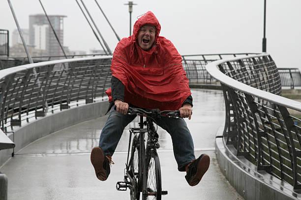 Man in rain on bike having fun stock photo