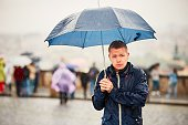 Rain in the city. Young man is holding blue umbrella during thunderstorm. Street of Prague, Czech Republic.