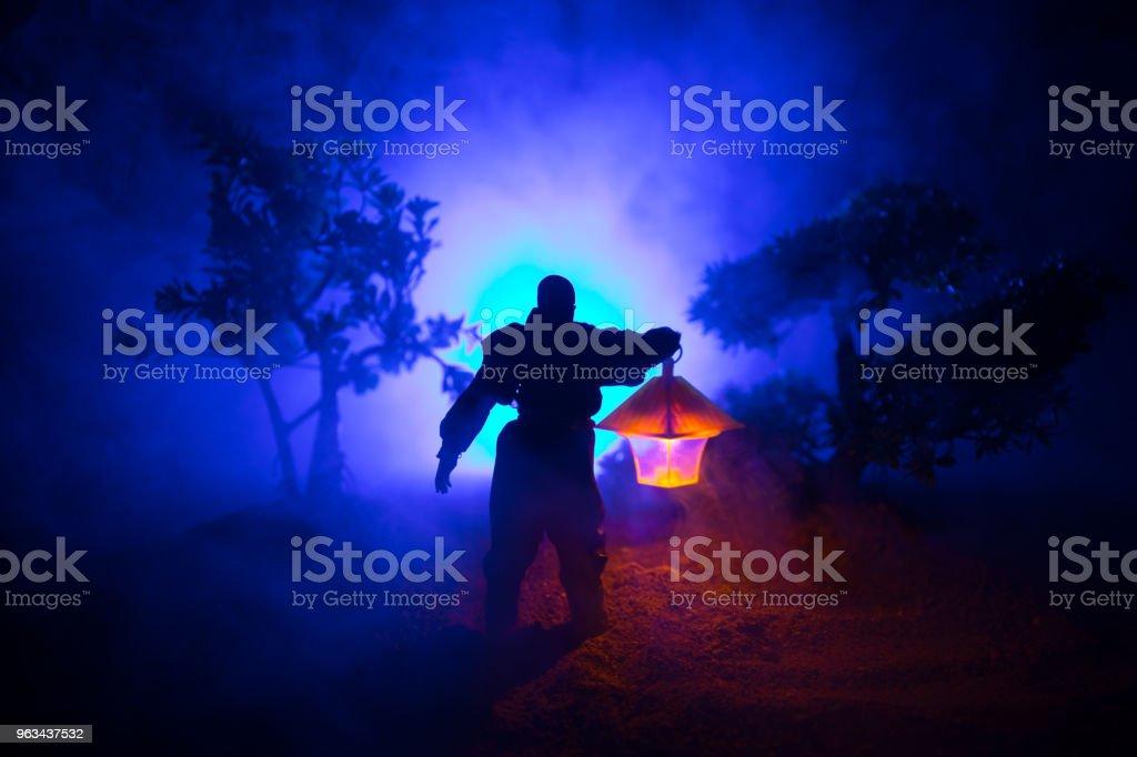 Homme en imperméable venant de la sombre forêt rougeoyante lanterne dans son concept de la main. Silhouette d'un tueur d'horreur avec lampe - Photo de Adulte libre de droits