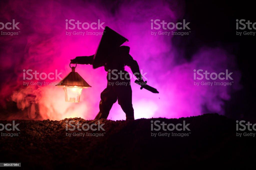 Mannen i regnrock kommer från mörka skogen med glödande lykta i sin hand-konceptet. Silhuetten av en skräck mördare med lampa. Dekoration - Royaltyfri Dimma Bildbanksbilder