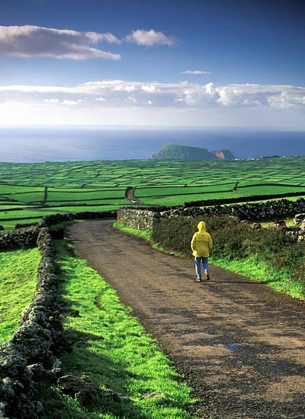 Mann mit Regenmantel entlang grüne Felder und Hügel mit üppigen – Foto
