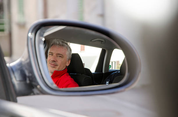 Man in rearview mirror stock photo