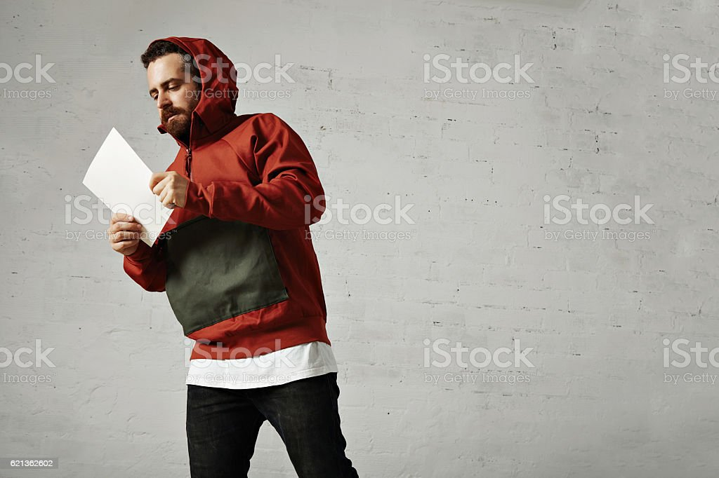 Man in red anorak with white sheet of paper stock photo