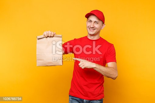 istock Man in red cap, t-shirt giving fast food order isolated on yellow background. Male employee courier hold empty paper packet with food. Products delivery from shop or restaurant to home. Copy space. 1026765734